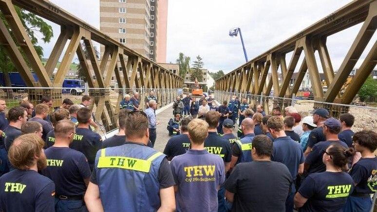 Helfer des Technischen Hilfswerks (THW) übergeben eine von ihnen errichtete Behelfsbrücke. Foto: Thomas Frey/dpa