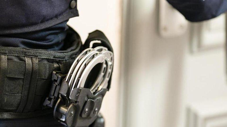 Handschellen sind an einem Gürtel eines Beamten befestigt. Foto: Frank Molter/dpa/Archivbild