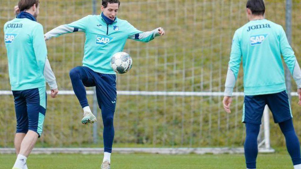 Hoffenheims Sebastian Rudy (M) mit Mannschaftskollegen während des Aufwärmtrainings. Foto: Uwe Anspach/dpa/Archivbild