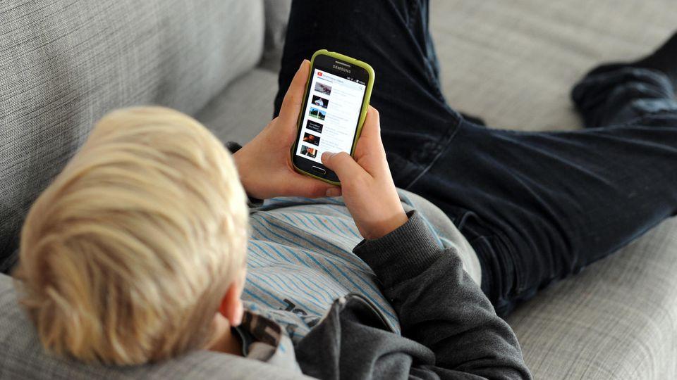 ARCHIV - ILLUSTRATION - Ein Jugendlicher betrachtet am 09.12.2014 in München (Bayern) Inhalte der Videoplattform «Youtube» auf seinem Smartphone (gestellte Szene). Foto: Tobias Hase/dpa (zu dpa: «Handy stattTabak: Mehr Jugendlichen droht Internetsuc