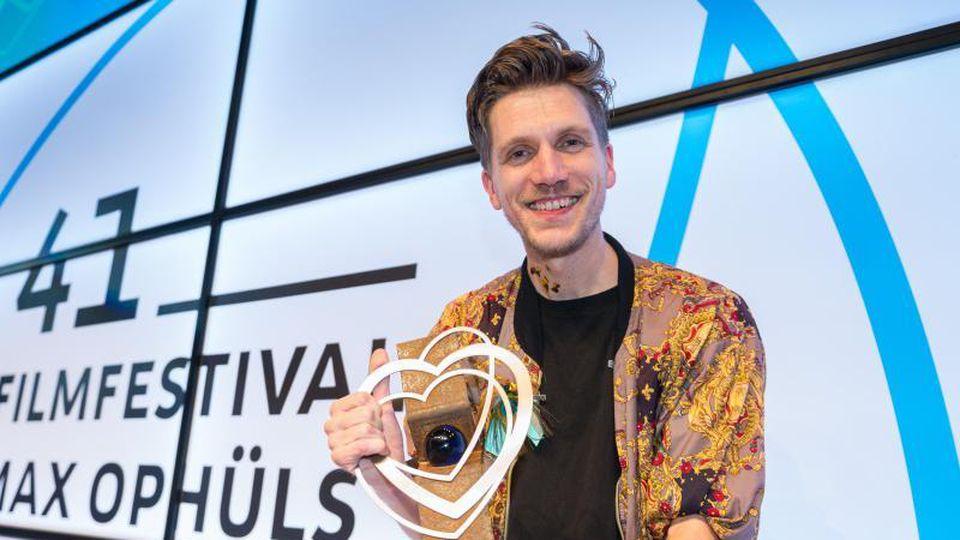 """Der Regisseur des Films """"Neubau"""", Johannes Maria Schmit, hält seine Trophäe in der Hand. Foto: Oliver Dietze/dpa"""