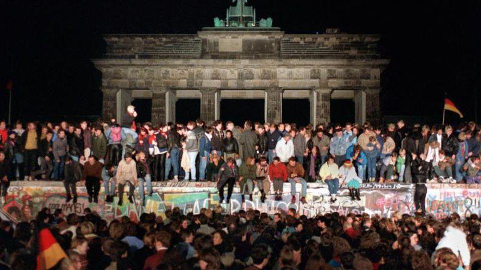 Jubelnde Menschen auf der Berliner Mauer am Brandenburger Tor 1989. Foto: Wolfgang Kumm/dpa/Archivbild