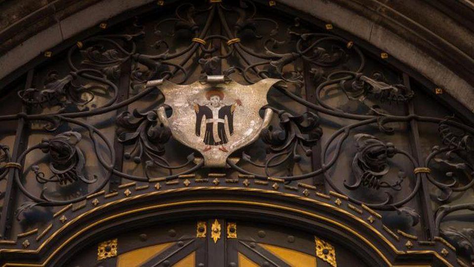 """Das Wappen mit dem """"Münchner Kindl"""" hängt über der Tür des Rathauses in der bayerischen Landeshauptstadt. Foto: Peter Kneffel/Archiv"""