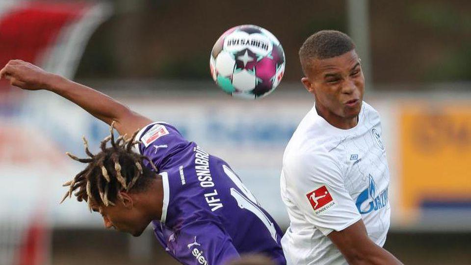 Der Osnabrücker Etienne Amenyido und der Schalker Malick Thiaw (l-r.) im Duell um den Ball. Foto: Friso Gentsch/dpa
