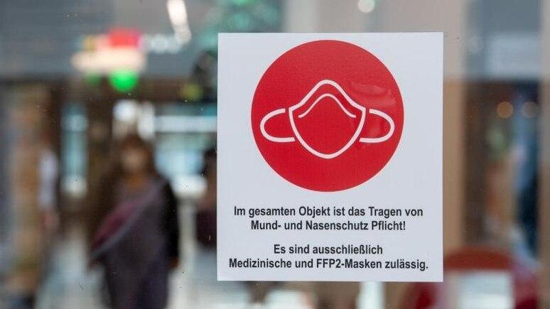 Ein Schild am Eingang zu einer Einkaufspassage weist auf das Tragen von Mund- und Nasenschutz hin. Foto: Hendrik Schmidt/dpa-Zentralbild/dpa