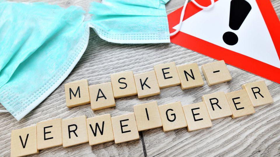 Zerrissener Mundschutz, Warnschild und Schriftzug Masken-Verweigerer *** Torn face mask, warning sign and lettering Mas