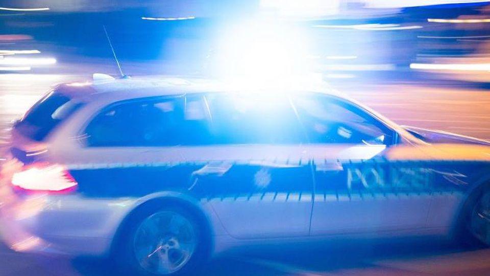 Ein Polizeiauto fährt unter Einsatz von Blaulicht und Sirene eine Straße entlang. Foto: Lino Mirgeler/dpa/Archiv