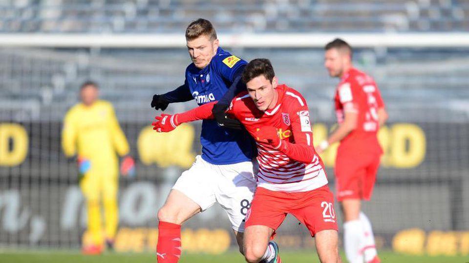 Kiels Alexander Mühling (l) und Regensburgs Maximilian Thalhammer kämpfen um den Ball. Foto: Daniel Bockwoldt/Archiv