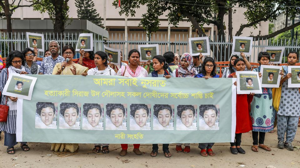 In this photo taken on April 12, 2019 Bangladeshi women hold banners and photographs of schoolgirl Nusrat Jahan Rafi at a protest in Dhaka, following her murder by being set on fire after she had reported a sexual assault. - A schoolgirl was burned t