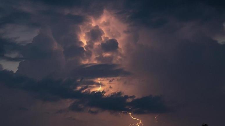 Ein Blitz hellt hinter dunklen Wolken auf. Foto: Fabian Sommer/dpa/Symbolbild