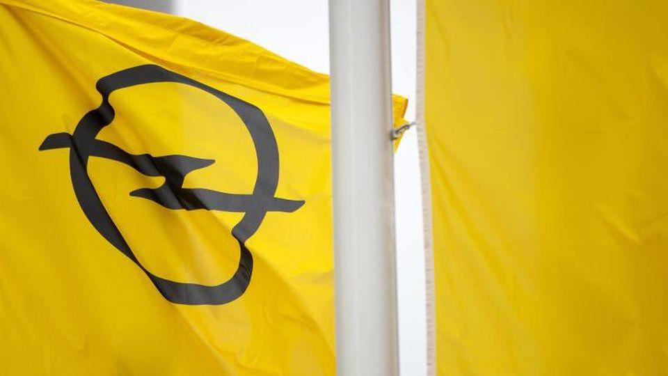Eine Fahne mit dem Opel-Logo. Foto: Michael Reichel/dpa/Archivbild