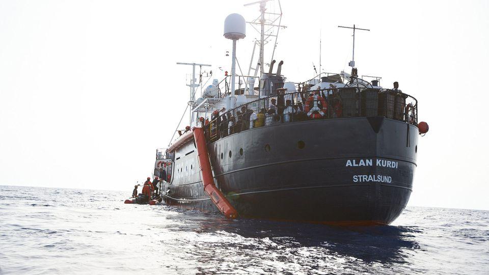"""HANDOUT - 05.07.2019, ---: Flüchtlinge werden vor der Küste von Libyen von Mitgliedern der Rettungsorganisation Sea-Eye (l) auf deren Hilfsschiff """"Alan Kurdi"""" gebracht. Foto: Fabian Heinz/Sea-Eye/dpa - ACHTUNG: Nur zur redaktionellen Verwendung im Zu"""