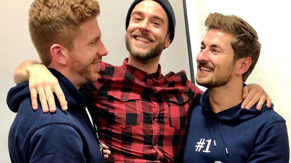 Podcast-Host Eric Stroh (m.) wird auf Händen von Lars Tönsfeuerborn (l.) und Prince Charming Nicolas Puschmann (r.) getragen.