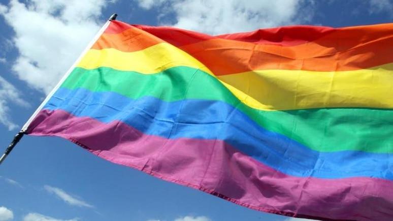 Eine Regenbogenfahne weht während eines CSD-Umzugs. Foto: picture alliance/Wolfgang Kumm/dpa/Symbolbild
