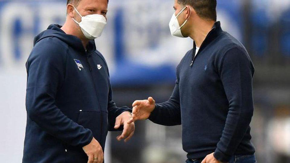 Herthas Trainer Pal Dardai (l) und Schalkes Trainer Dimitrios Grammozis unterhalten sich. Foto: Martin Meissner/AP-Pool/dpa