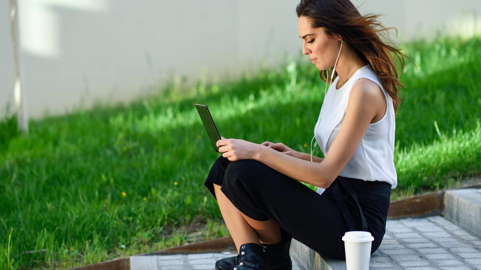Young businesswoman having a videoconference with her laptop computer sitting on urban steps outdoors.. Middle-age busin