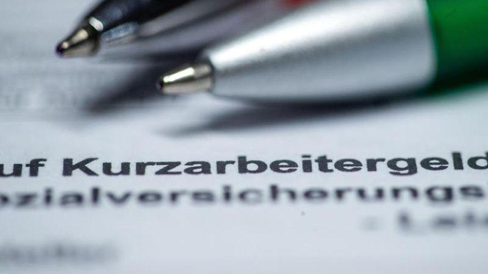 Zwei Kugelschreiber liegen auf einem Antragsformular für Kurzarbeitergeld. Foto: Jens Büttner/dpa-Zentralbild/dpa/Illustration