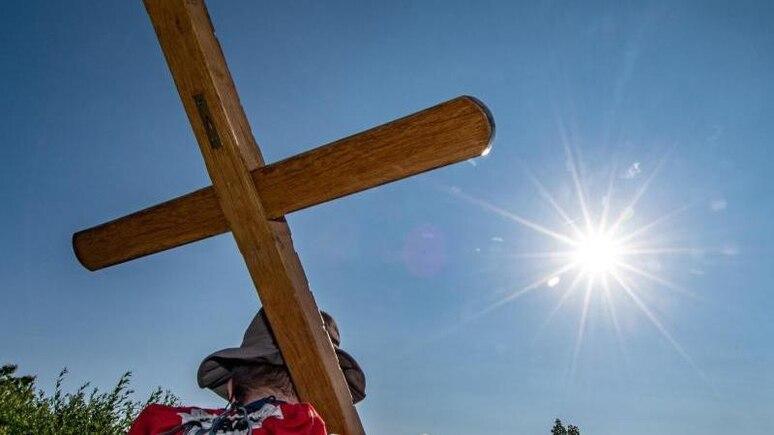 Ein Pilger trägt ein Holzkreuz. Foto: Armin Weigel/dpa/Archivbild