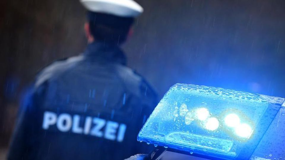 Ein Polizist steht mit dem Rücken zu einem Streifenwagen. Foto: Karl-Josef Hildenbrand/dpa/Symbolbild
