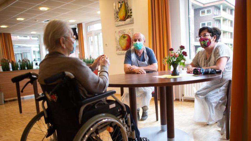 Zwei Angehörige besuchen eine Frau, die im Rollstuhl sitzt. Foto: Jonas Güttler/dpa/Symbolbild