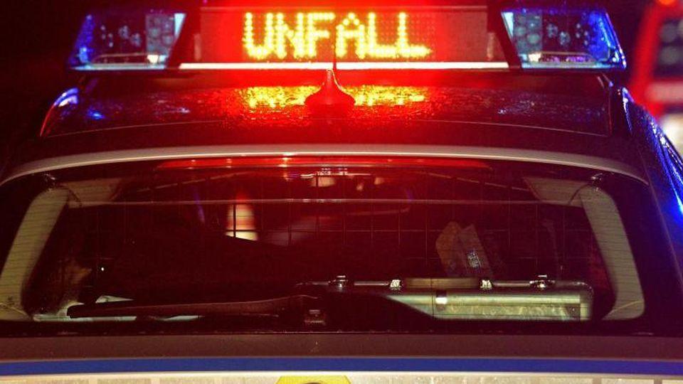 """Blaulicht und der LED- Schriftzug """"Unfall"""" leuchten auf dem nassen Dach eines Polizestreifenwagens. Foto: Stefan Puchner/dpa/Symbolbild"""