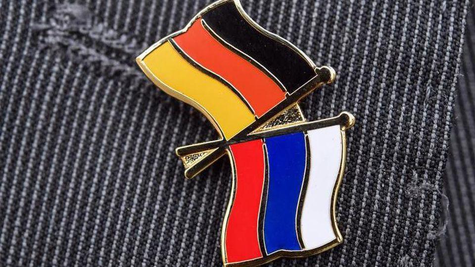 Ein Mann trägt einen Anstecker mit einer kleinen deutschen und russischen Flagge an seinem Sakko. Foto: Patrick Pleul/dpa-Zentralbild/dpa/Archivbild