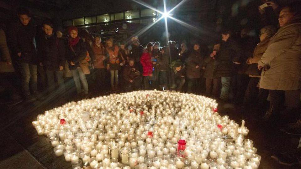 Pforzheimer auf dem Markplatz neben brennenden Kerzen zum Gedenken an die Zerstörung der Stadt. Foto: picture alliance/dpa/Archivbild