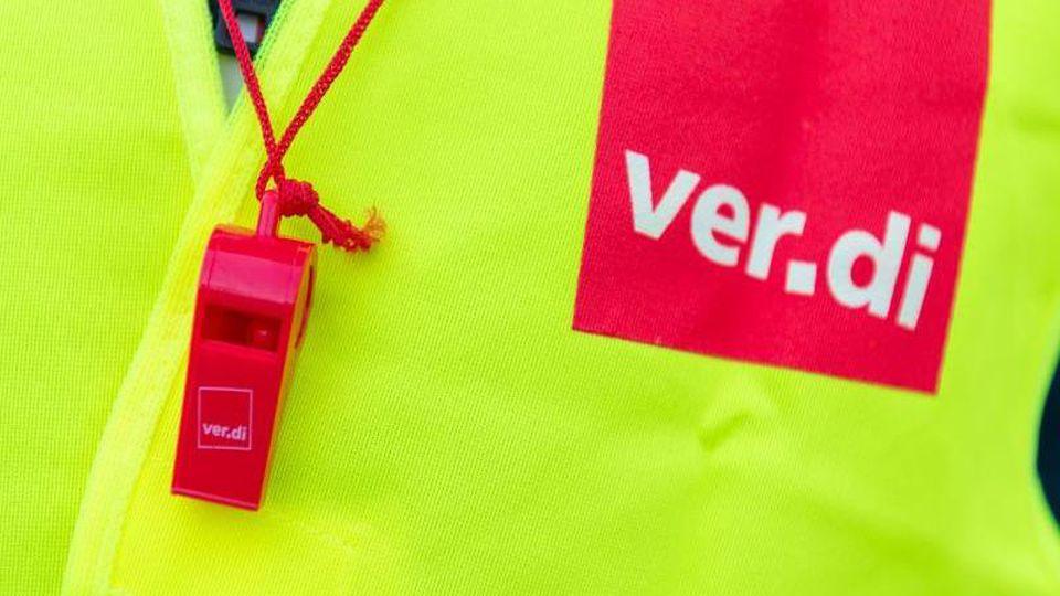 Ein Streikender trägt eine Warnweste mit dem Verdi-Logo und eine rote Trillerpfeife. Foto: Christophe Gateau/dpa/Archivbild