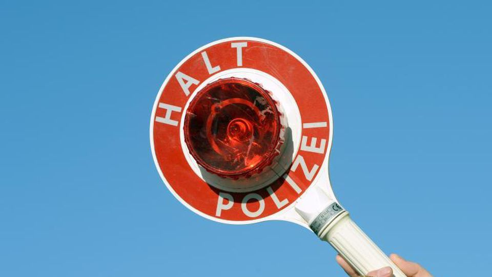 """Eine Kelle mit der Aufschrift: """"Halt Polizei"""" wird hoch gehalten. Foto: Ralf Hirschberger/dpa-Zentralbild/dpa/Symbolbild"""