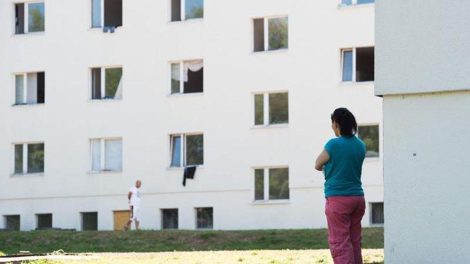 Eine Bewohnerin der Erstaufnahmestelle Suhl telefoniert vor einem Wohnheim. Foto: Sebastian Kahnert/dpa-Zentralbild/dpa/Archivbild