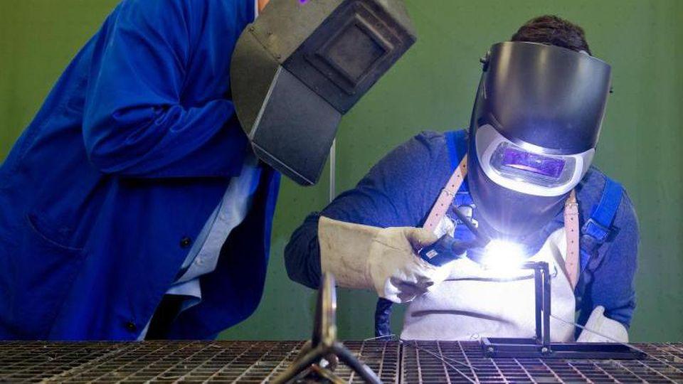 Ein Auszubildender (r) setzt eine Schweißnaht an ein Metallteil. Foto: Daniel Bockwoldt/dpa