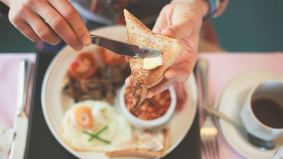 Closeup on a young woman's hands as she is having breakfast