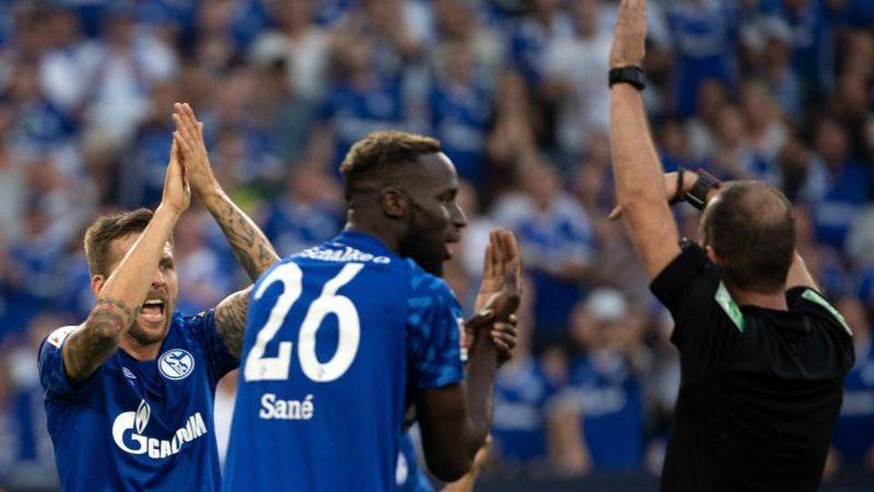 Schalkes Sane (M) und Burgstaller (l) beschweren sich bei Schiedsrichter Fritz über ein nicht gegebenes Handspiel. Foto: Federico Gambarini