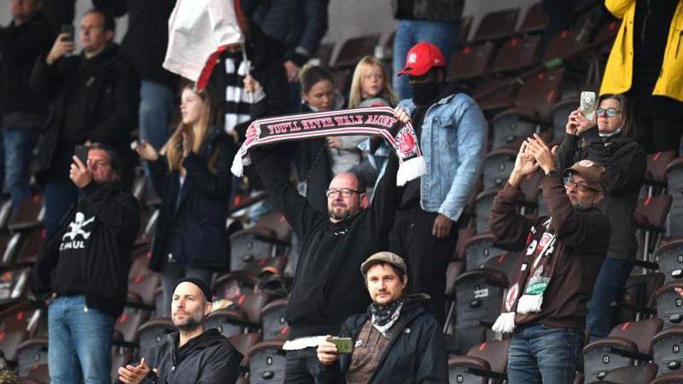 Fans des FC St. Pauli verfolgen das Spiel auf der Tribüne. Foto: Daniel Reinhardt/dpa