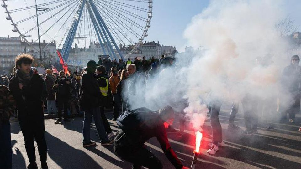 Ein Demonstrant zündet Pyrotechnik während einer Demonstration am Platz Bellecour. Foto: Robert Michael/dpa-Zentralbild/dpa