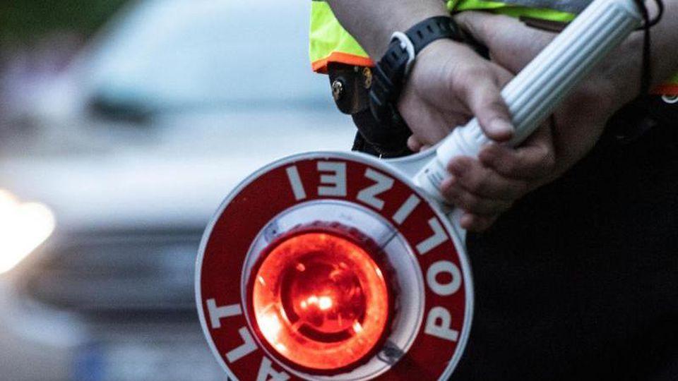 Ein Polizist hält an einer Kontrollstelle eine Winkerkelle in der Hand. Foto: Paul Zinken/dpa/ZB/Symbolbild