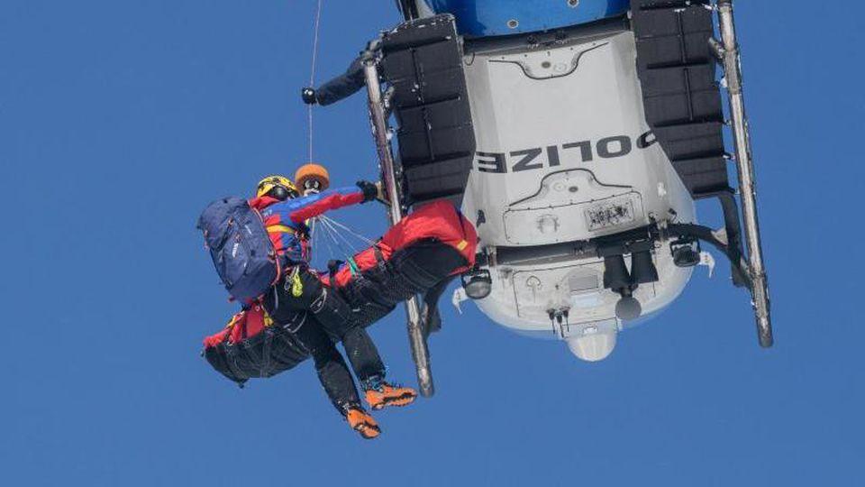 Ein Bergwachtmann und eine gerettete Person werden in einen Polizeihubschrauber gezogen. Foto:Matthias Balk/Archivbild