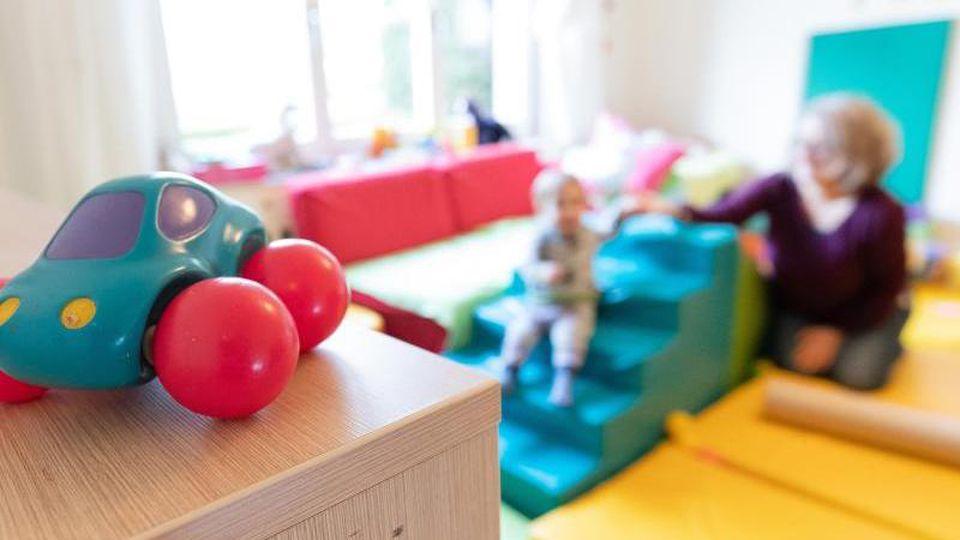 Ein Spielzeugauto ist in den Räumen einer Kindertagesstätte zu sehen, im Hintergrund ein Kind zusammen mit einer Erzieherin. Foto: Friso Gentsch/dpa/Illustration