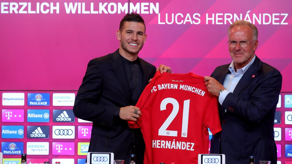 MUNICH, GERMANY - JULY 08: Lucas Hernandez (L) of FC Bayern Muenchen and Karl-Heinz Rummenigge, CEO of FC Bayern Muenchen, pose with Hernandez jersey during a press conference to present new signing Lucas Hernandez at Allianz Arena on July 08, 2019 i