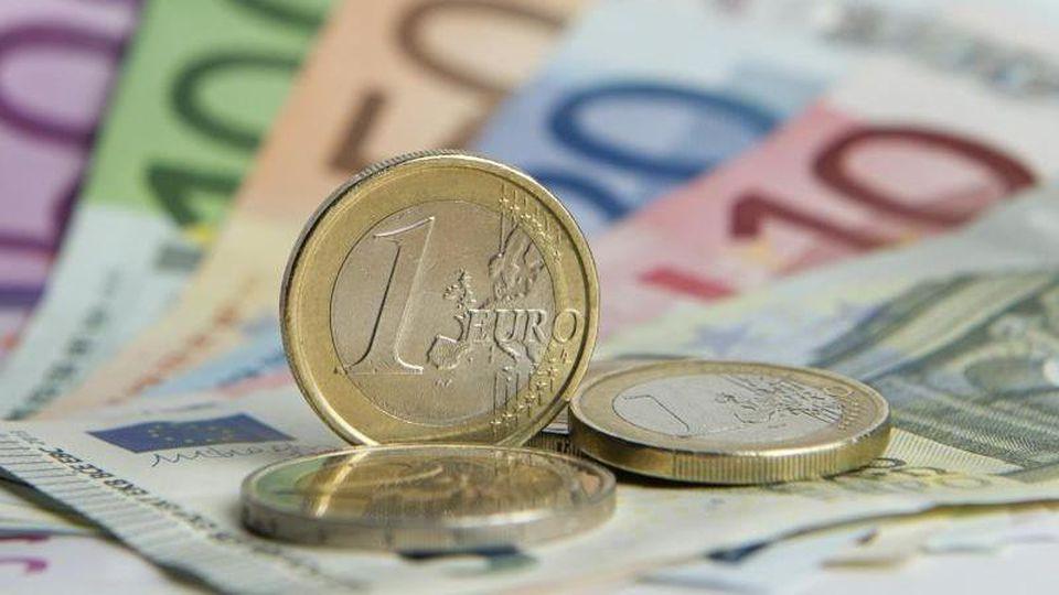 Euro-Münzen auf Euro-Banknoten. Foto: Daniel Reinhardt/dpa/Symbolbild