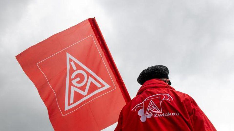 Eine Frau demonstriert mit einer Fahne der IG Metall. Foto: Hendrik Schmidt/dpa-Zentralbild/dpa/Archivbild