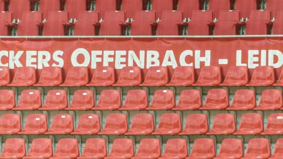 """Leere Sitzreihen und ein """"Kickers Offenbach"""" Schriftzug im Sparda-Bank-Hessen-Stadion. Foto: Boris Roessler/dpa/Archivbild"""