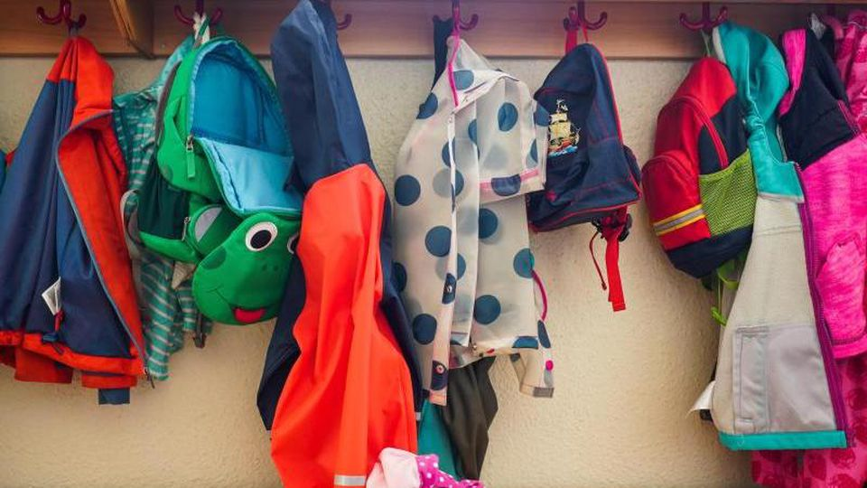 Jacken und Rucksäcke hängen an der Garderobe einer Kita. Foto: Jörg Carstensen/dpa/Archivbild