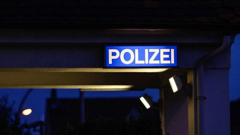 """Ein Schild mit der Aufschrift """"Polizei"""" leuchtet am Eingangsbereich der Polizeistation. Foto: Silas Stein/dpa/Symbolbild"""