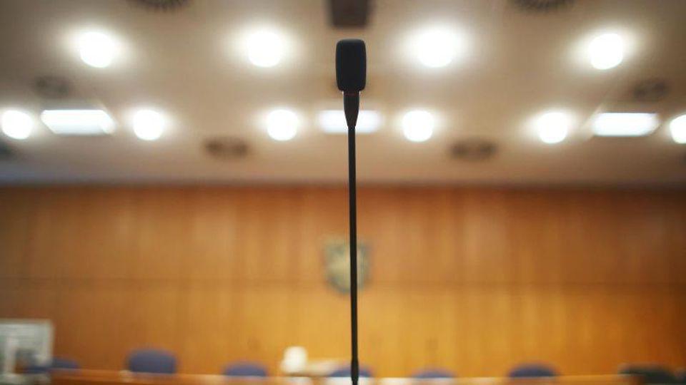 Am Platz des Zeugentisches steht in einem Verhandlungssaal im Landgericht ein Mikrofon. Foto: Fredrik von Erichsen/dpa