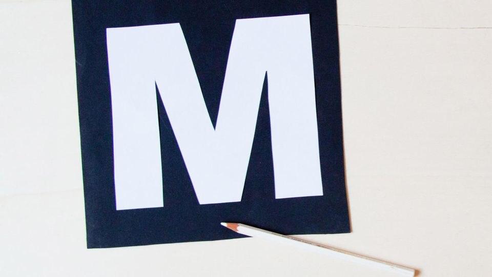 Buchstaben und Stern werden auf das feste Papier gezeichnet und ausgeschnitten