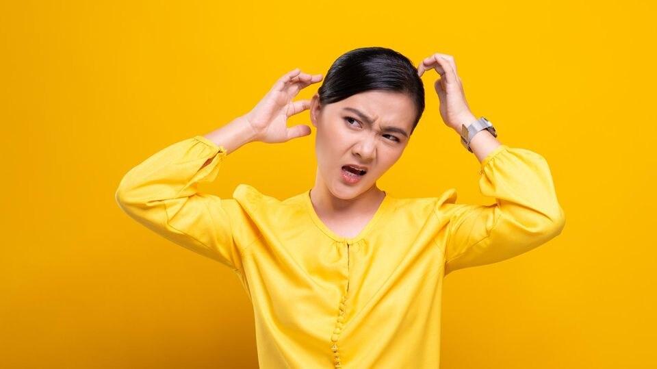 Die Kopfhaut juckt: Frau kratzt sich den Kopf