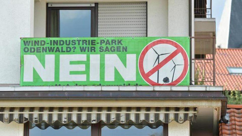 """Ein Transparent mit der Aufschrift """"Wind-Industrie-Park Odenwald? Wir sagen Nein"""" hängt an einem Wohnhaus. Foto: Uwe Anspach/Archivbild"""