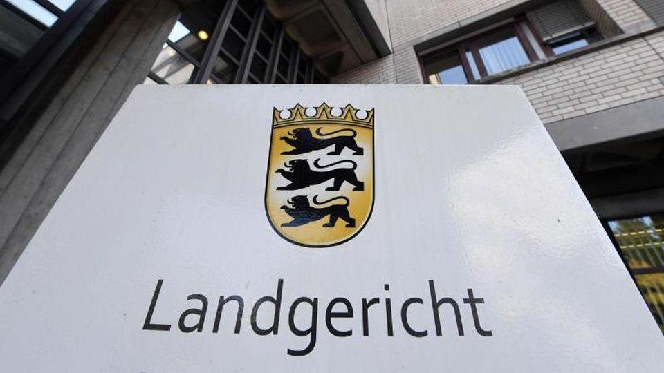 Ein Hinweisschild vor dem Landgericht Baden-Baden und dem Landeswappen von Baden-Württemberg. Foto: Uli Deck/dpa