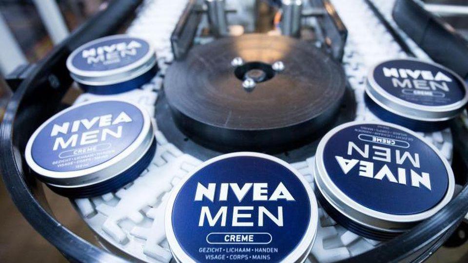 """Cremedosen der Sorte """"Nivea Men"""" sind im Produktionswerk der Beiersdorf AG auf einem Förderband zu sehen. Foto: Christian Charisius/Archiv"""